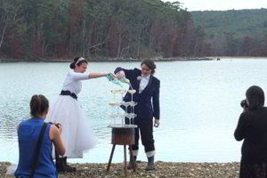 Stunning brides pouring champagne down on Mickeys Bay in front of Bruny Island Lodge