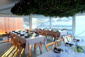 Tables set up under a marquee for a wedding reception at Bruny Island Lodge