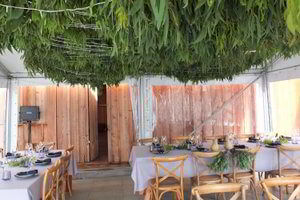Tables set up under a canopy for a wedding reception at Bruny Island Lodge. Eucalyptus leaves formed a hanging canopy.