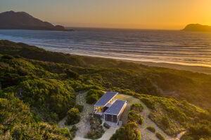 Cloudy Bay Beach House as the sun sets over Cape Bruny