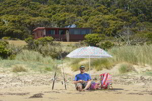 Relaxing on the beach with the cabin in the background