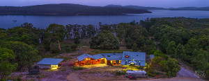 Overhead view of Bruny Island Lodge at night, with the D'Entrecasteaux Channel in the background and Greater Taylors Bay