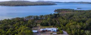 Daytime aerial view of Bruny Island Lodge, with Curlew Island in the D'Entrecasteaux Channel in the background