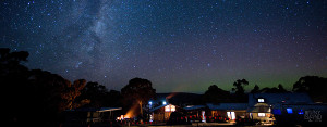 Bruny Island Lodge at nighttime with a spectacular night sky background containing the Milky Way and southern Aurora Australis