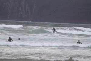 A group of Surfers catching waves at Cloudy Bay.